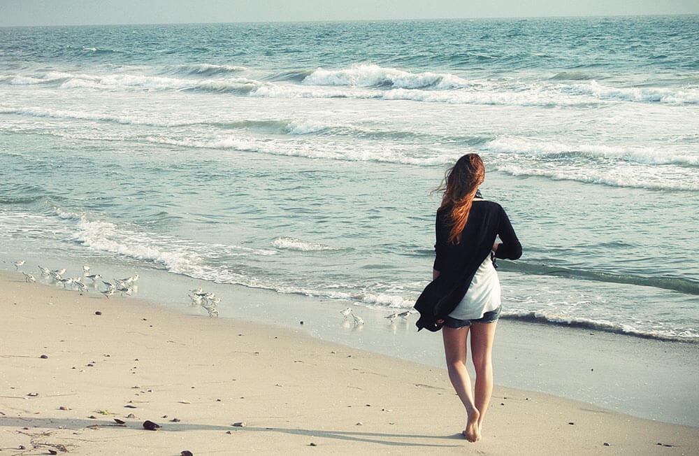Девушка прогуливается на берегу моря