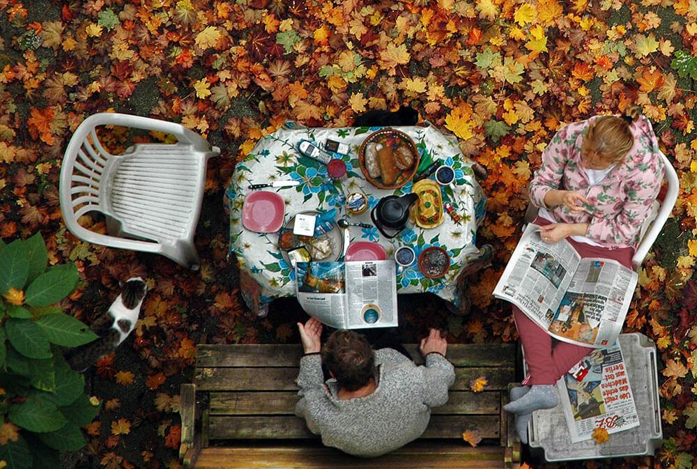 люди сидят осенью за столом